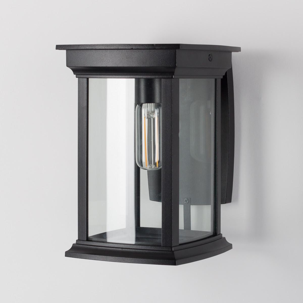 Zwarte wandlamp voor buiten, vierkante muursteun, lantaarnkap met zwart frame en heldere ruitjes, lichtbron boven in de kap, zichtbaar in het armatuur